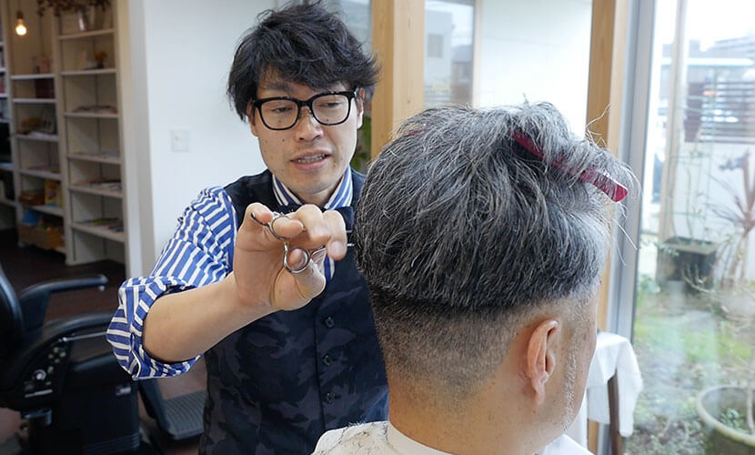 50代の男性をカットする店長田中さん